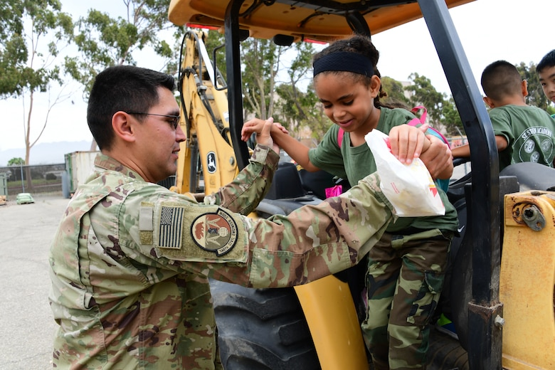 U.S. Air National Guard Staff Sgt. Guillermo Diaz Garcia provides a tour of heavy equipment used by the 146th Civil Engineer Squadron to a group of children attending students attending a summer camp with St. Stephen's Academy at the Channel Islands Air National Guard Station, Port Hueneme, CA. July 25, 2019. (U.S. Air National Guard photo by Tech. Sgt. Nieko Carzis)