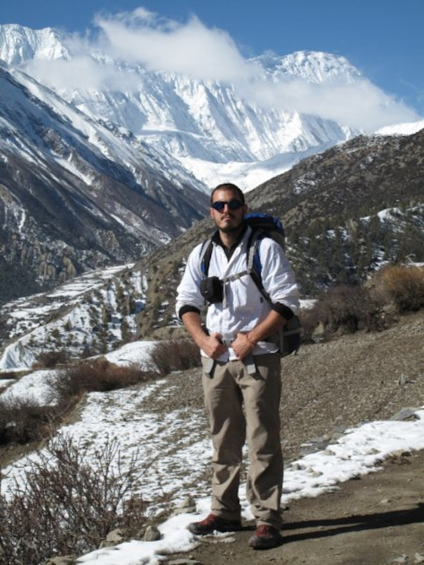 Airman stands on mountains in hiking gear.