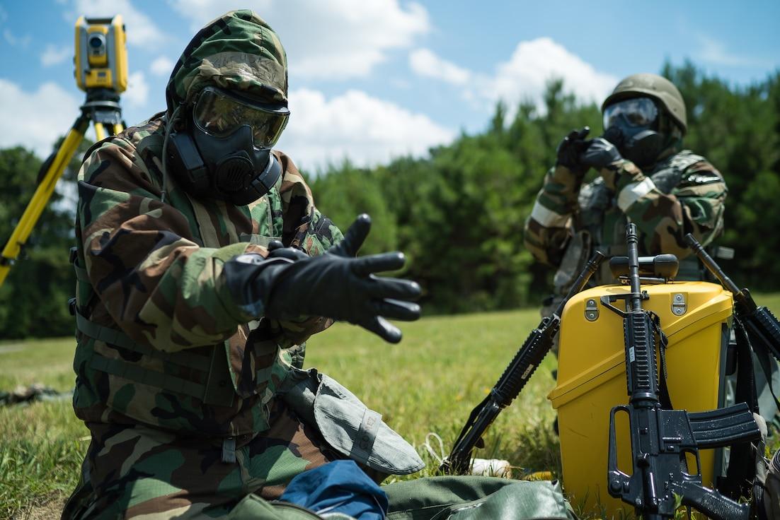 Senior Airmen put on mission oriented protective posture gear