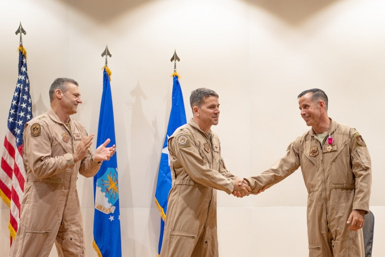 Col. Jason Hokaj, right, and Col. Thomas Wolfe shake hands during the Air Warfare Center change of command ceremony June 19, 2019, at Al Dhafra Air Base, United Arab Emirates.