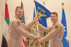 Col. Thomas Wolfe, right, accepts command of the Air Warfare Center by taking the guidon to Lt. Gen. Joseph T. Guastella, U.S. Air Force Central Command commander, June 19, 2019, at Al Dhafra Air Base, United Arab Emirates.