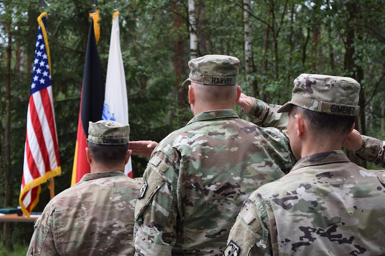 After three years in the position, Col. Christopher Varhola relinquished command of the 2500th Digital Liaison Detachment to Col. Gregory Gimenez during a change of command ceremony Aug. 17 at Camp Normandy, Grafenwoehr, Germany.