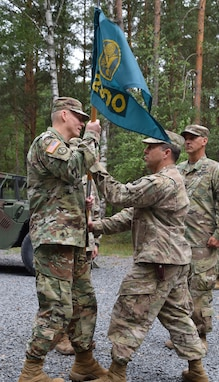 Col. Christopher Varhola passes the 2500th Digital Liaison Detchment colors to Brig. Gen. Michael T. Harvey symbolizing his relinquishment of command during a change of command ceremony Aug. 17 at Camp Normandy, Grafenwoehr, Germany. After three years in the position, Varhola passed command of the 2500th DLD to Col. Gregory Gimenez.