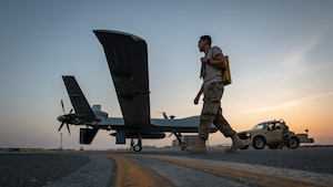 Maintainers with the 386th Expeditionary Aircraft Maintenance Squadron tow a U.S. Air Force MQ-9 Reaper remotely piloted aircraft into position for an engine test prior to Intelligence, Surveillance, and Reconnaissance operations at Ali Al Salem Air Base, Kuwait, July 23, 2019. Reaper's are maintained, launched and recovered from deployed locations, but are remotely operated from bases in the United States during ISR operations around the world. (U.S. Air Force Photo by Tech. Sgt. Michael Mason, tail number obscured for operational security)