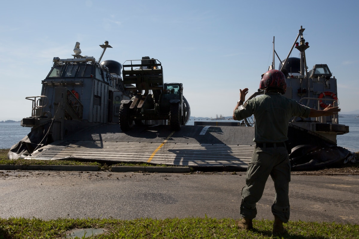 A U.S. Navy beach master unloads heavy equipment from a U.S. Navy landing craft.