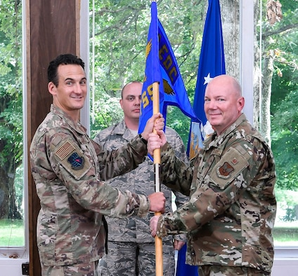 AEDC Commander Col. Jeffrey Geraghty, left, passes the Test System Sustainment Division guidon to incoming division chief Lt. Col. Jeffrey Burdette during an Assumption of Leadership Ceremony Aug. 9 at the Arnold Lakeside Center on Arnold Air Force Base. (U.S. Air Force photo by Jill Pickett)