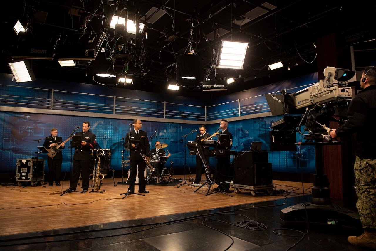 Musicians play instruments in a studio on a stage with overhead lights.
