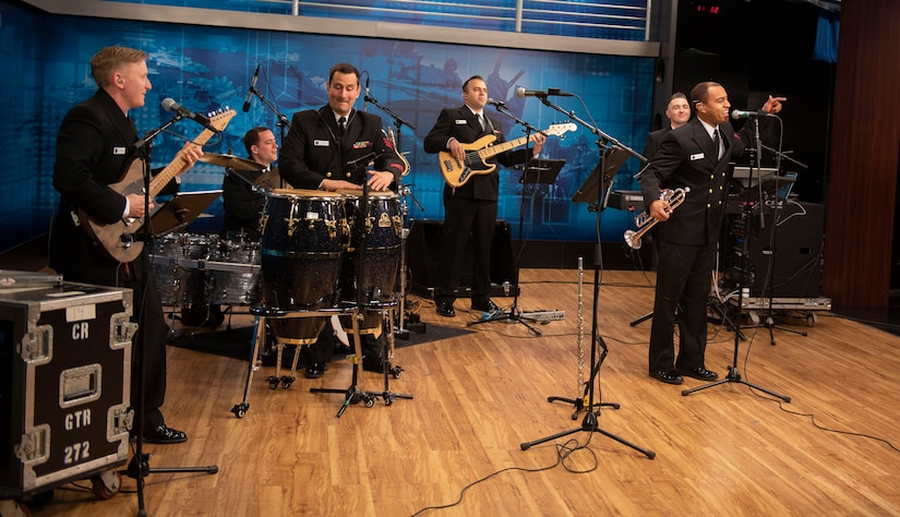 Men in Navy uniforms play instruments and sing into microphones.