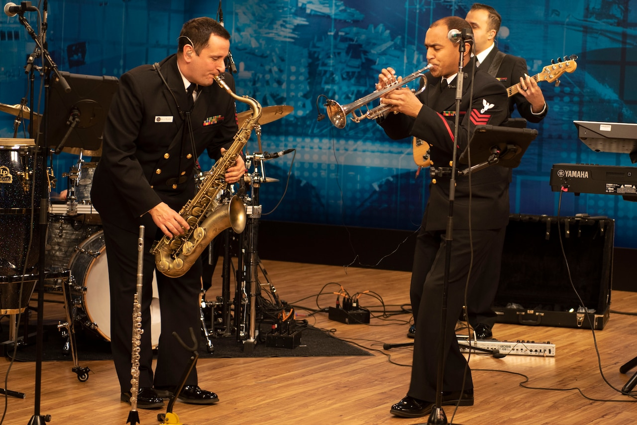 Members of a Navy band play instruments.
