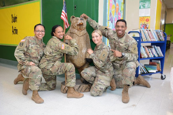 Masters of social work students 2nd Lt. Marcela Mcduffie, 2nd Lt. Camethia Russell-Morris, 2nd Lt. Jamie Webb, and 2nd Lt. Jaron Stubbs pose in front of the Briscoe Elementary school bear mascot Aug. 8, which was donated to the school by the 187th MED BN in 2016.