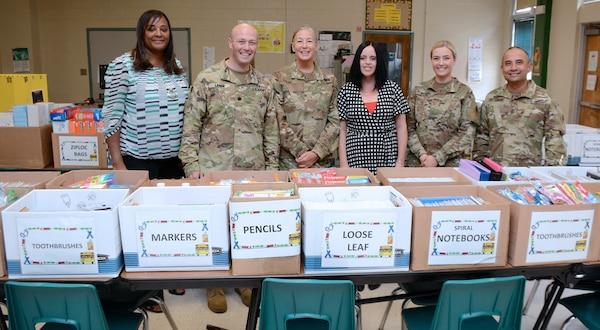 (From left) Lorraine Harper, a 187th Medical Battalion civilian employee; Michelle Ayala, Briscoe Elementary School social worker; Lt. Col. Paul Lang, commander, 187th MED BN; Maj. Debra Stone, MSW executive officer; Jennifer Emerson, Briscoe Elementary School principal; 2nd Lt. Jamie Webb, MSW student, 1st Sgt. Roman De Vega, Company A, 187th MED BN; and Carlos Flores, 187th MED BN civilian employee, pose in front of more than $10,000 worth of donated school supplies Aug. 8.