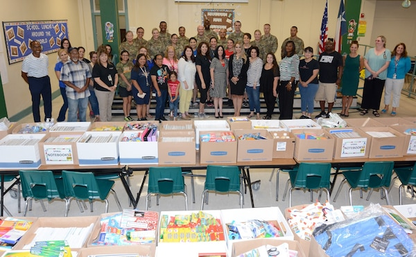 Briscoe Elementary School staff and Soldiers from the 187th Medical Battalion pose in front of more than $10,000 worth of donated school supplies Aug. 8.