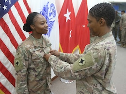 Spc. Ravan Lee, 184th Sustainment Command, is pinned the rank of sergeant by her step-mother, Lt.  Col. Annie Merle Lee, 184th Sustainment Command, at Camp Arifan, Kuwait, Aug. 14, 2019.