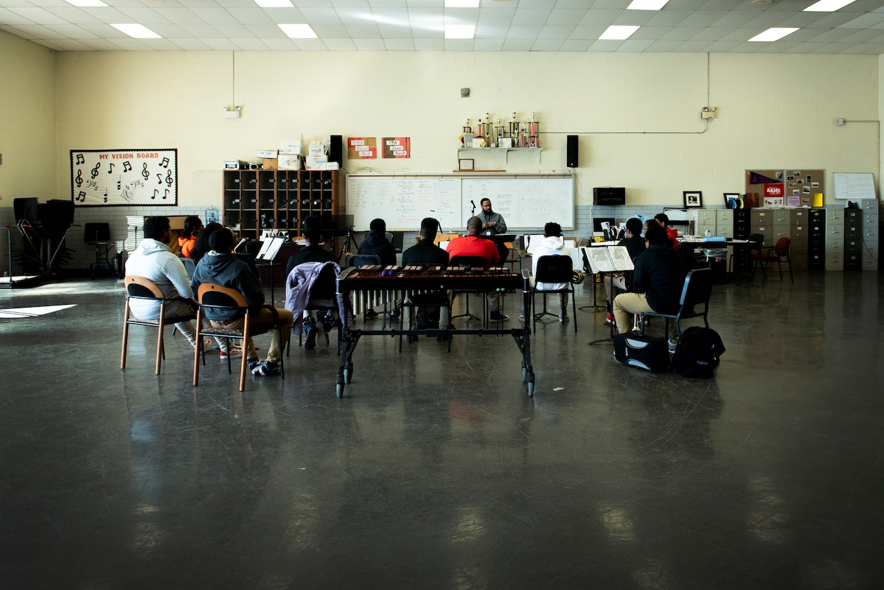 Students in a high school music class huddle around the teacher.