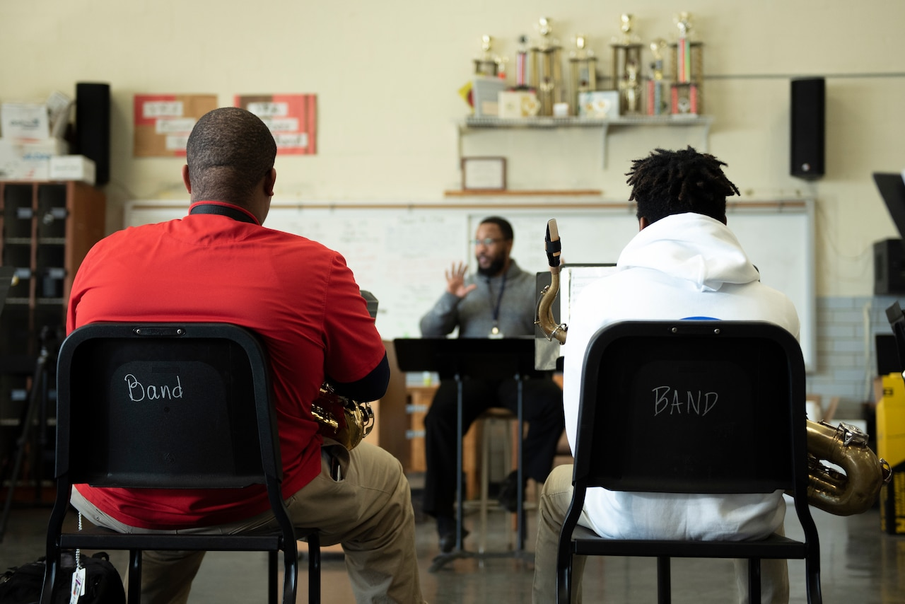 A teacher seen through two students sitting with their backs to the camera.