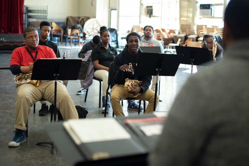Students holding instruments with music stands in front them sit in a classroom.