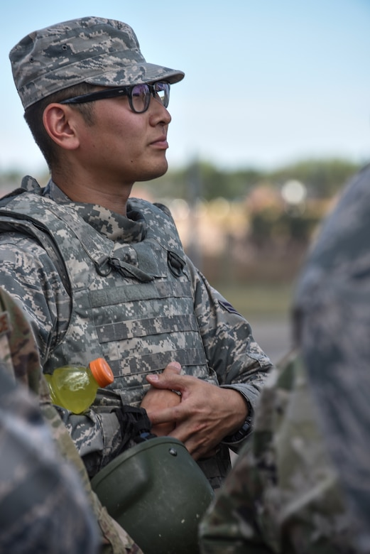 Airman 1st Class Daniel Masahiro Kim, 90th Civil Engineer Squadron power production, listens to a briefing before participating in a tactical convoy exercise during a 90th Mission Support Group Warrior Day Aug. 15, 2019, on F.E. Warren Air Force Base, Wyo. The convoy ran Airmen through a village, allowing them to participate in a simulated rescue and recovery of an injured pilot. (U.S. Air Force photo by Senior Airman Abbigayle Williams)