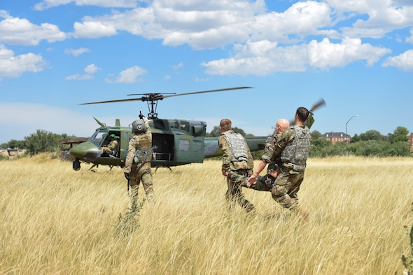 90th Mission Support Group Airmen carried an injured dummy for emergency helicopter evacuation in a tactical convoy exercise during a warrior day Aug. 15, 2019, on F.E. Warren Air Force Base, Wyo. The training allowed Airmen within the 90th MSG an opportunity to experience simulated convoy operations in a controlled environment. (U.S. Air Force photo by Senior Airman Abbigayle Williams)