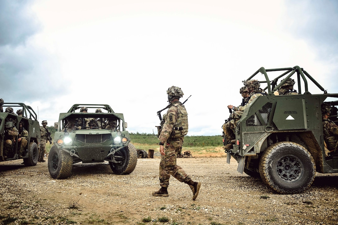 A soldier walks alongside soldiers riding in military vehicles.
