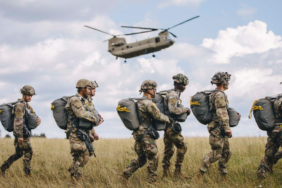 Soldiers walk in a line as a military aircraft flies above.