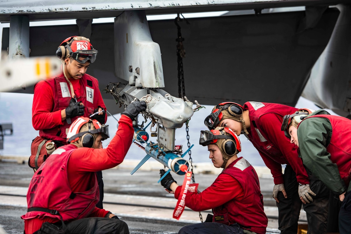 Sailors load a weapon onto an aircraft.