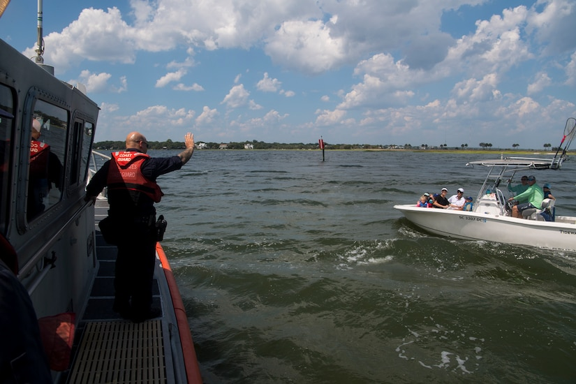 U.S. Coast Guard Petty Officer 2nd Class James Sokol, a maritime enforcement specialist assigned to USCG Station Charleston, signals an approaching vessel while performing inspections in support of Operation SHRIMP and GRITS in Charleston Harbor, August 9, 2019. Operation SHRIMP and GRITS is an annual multi-jurisdiction and multi-state maritime  law enforcement operation that promotes safety to recreational and commercial boaters traveling along the water across South Carolina, North Carolina, Georgia and Florida. Approximately 104 different agencies in the four states participated in the operation with the U.S. Coast Guard, covering about 500 miles of coastline.
