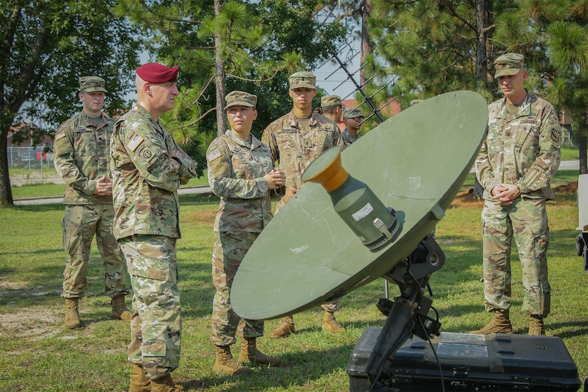 Troops stand around satellite dish