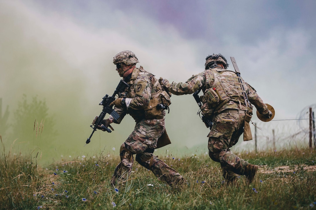 Two soldiers run with smoke in the air.