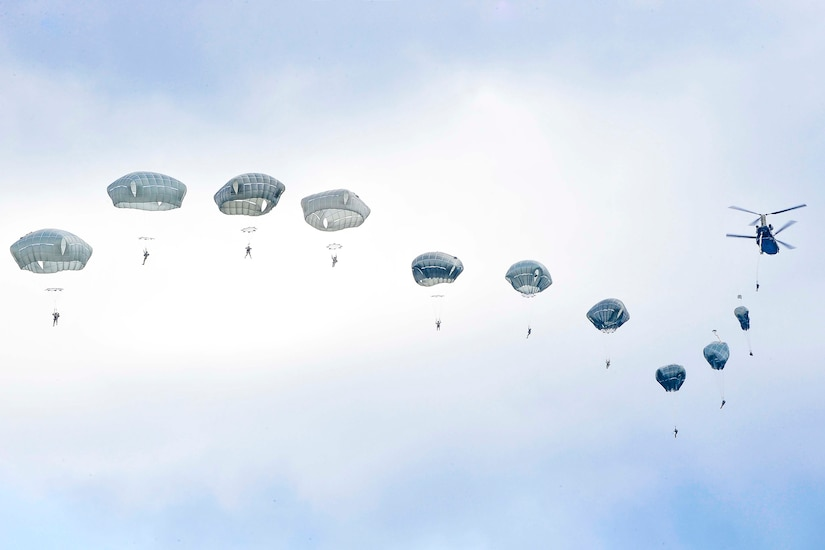 Paratroopers  jump out of an aircraft in a row.