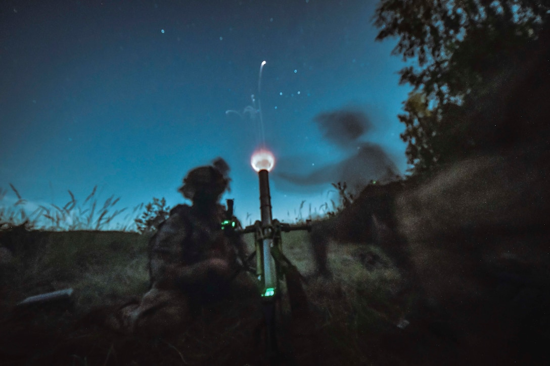 Soldiers fire a military weapon at night.