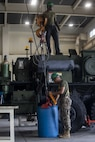 U.S. Marine Corps Cpl. Alexander Roserieerden, bottom, and Lance Cpl. Marcelius Williams prepare to lift a barrel of radiator fluid during preventative maintenance on Camp Kinser, Okinawa, Japan, August 16, 2019. The Marines with Motor Transportation Maintenance Company regularly conduct preventative maintenance on vehicles to ensure serviceability. Roserieerden, a native of the U.S. Virgin Islands, is a motor transportation technician with MTM Co., 3rd Maintenance Battalion, Combat Logistics Regiment 35, 3rd Marine Logistics Group. Williams, a native of Detroit, Michigan, is a motor transportation technician with MTM Co., 3rd Maint. Bn., CLR-35, 3rd MLG. (U.S. Marine Corps photo by Lance Cpl. Armando Elizalde)