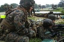 U.S. Marine Corps Cpl. Michael Lien, left, instructs Marines during a machine gun range on Range 7, Camp Hansen, Okinawa, Japan, June 20, 2019. During the range, Marines with Communications Company, Combat Logistics Regiment 37, 3rd Marine Logistics Group, trained to improve field communications skills while employing M249 light machine guns, M240B medium machine guns and .50 caliber machine guns. Lien, a native of Castaic, California, is a weapons instructor with Tactical Readiness and Training Platoon, CLR-37, 3rd MLG. (U.S. Marine Corps photo by Cpl. Joshua Pinkney)