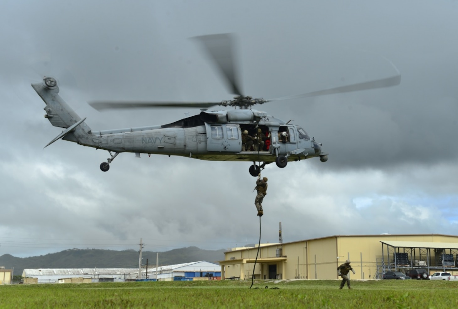 A U.S. Navy Sailor assigned to Explosive Ordnance Disposal Mobile Unit 5 (EODMU 5) fast-ropes from an MH-60S Seahawk helicopter during HYDROCRAB at Santa Rita, Guam, August 19, 2019. HYDRACRAB is quadrilateral exercise conducted by forces from Australia, Canada, New Zealand, and U.S. Naval forces. The purpose of this exercise is to prepare the participating Explosive Ordnance Disposal (EOD) forces to operate as an integrated, capable, and potent allied force ready to respond to a changing and complex maritime environment in the Indo-Pacific region.