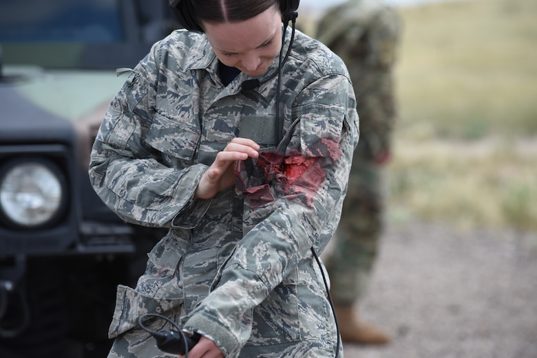 An Airman looks at her simulated wound after the conclusion of the 90th Mission Support Group's Warrior Day at F.E. Warren Air Force Base, Wyoming, Aug. 15, 2019. The purpose of the training day was to provide 90th Force Support Squadron Airmen with convoy operations knowledge, allowing them to fulfill a supporting role. (U.S. Air Force photo by Senior Airman Abbigayle Williams)