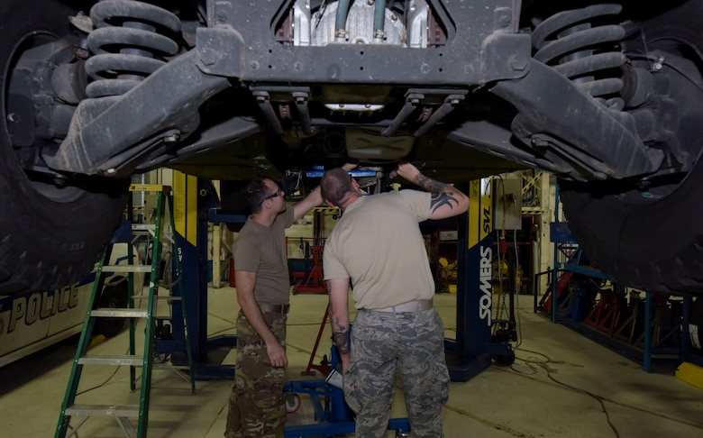 Texas Air National Guardsmen Airman 1st Class Ryan Doan, 221st Combat Communications Squadron vehicle mechanic, Naval Air Station Joint Reserve Base Fort Worth, Texas, left, and Master Sgt. Brandon Isam, 221st Combat Communications Squadron NCO-in-charge of vehicle maintenance, check the under carriage of a 100th Logistics Readiness Squadron assigned vehicle at RAF Mildenhall, England, July 30, 2019. The guardsmen conducted annual vehicle maintenance training with the 100 LRS here. (U.S. Air Force photo by Senior Airman Alexandria Lee)