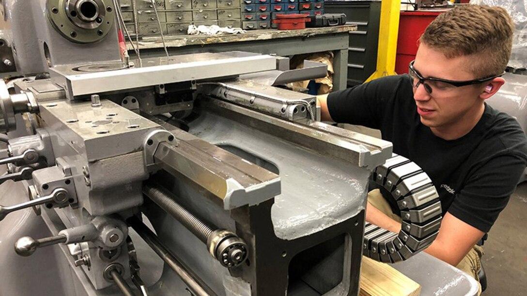 Production Machinery Mechanic Kristopher Nace refurbishes a Monarch EE Lathe