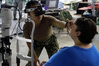 U.S. Navy Reserve Lt. Gillian Claveria-Oooms, optometrist, Expeditionary Medical Facility Dallas One, Ft. Worth, Texas, examines a patient at Innovative Readiness Training Appalachian Care 2019 at Wise County Fairgrounds, Wise, Va., Aug. 18, 2019.