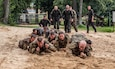 Soldiers from 278th Armored Cavalry Regiment along with Polish soldiers low crawl in the sand during day two of training for the Water Survival Course hosted by 15th Mechanized Brigade in Gizycko, Poland, Aug. 12, 2019.