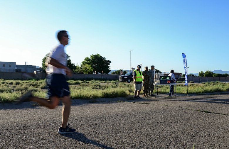 A member of the 377th Air Base Wing crosses the finish line during a Wing Tiger Run at Kirtland Air Force Base, N.M., August 16, 2019.  The Tiger Run is an opportunity for Airmen to display how Physical Fitness is one of the four pillars of Comprehensive Airman Fitness. (U.S. Air Force Photo by Airman 1st Class Kiana Pearson)