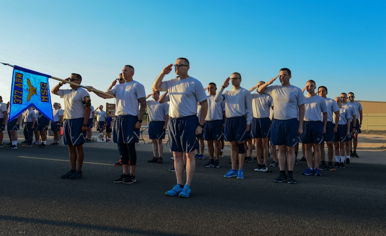 Members of 377th Mission Support Group stand in formation during revile before a Wing Tiger Run at Kirtland Air Force Base, N.M., August 16, 2019.  Wing Tiger Runs are held quarterly to bring different units of the 377th Air Base Wing together to increase morale and esprit de corps. (U.S. Air Force Photo by Airman 1st Class Kiana Pearson)