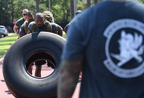 U.S. Air Force Staff Sgt. Thane Sandy, 81st Security Forces Squadron combat arms instructor, flips a tire during the 81st SFS Defender's Challenge Ruck on the Crotwell Track on Keesler Air Force Base, Mississippi, Aug. 16, 2019. The competition, consisting of 11 four-person teams, completing seven obstacles, was one of several events in recognition of The Year of the Defender. (U.S. Air Force photo by Kemberly Groue)