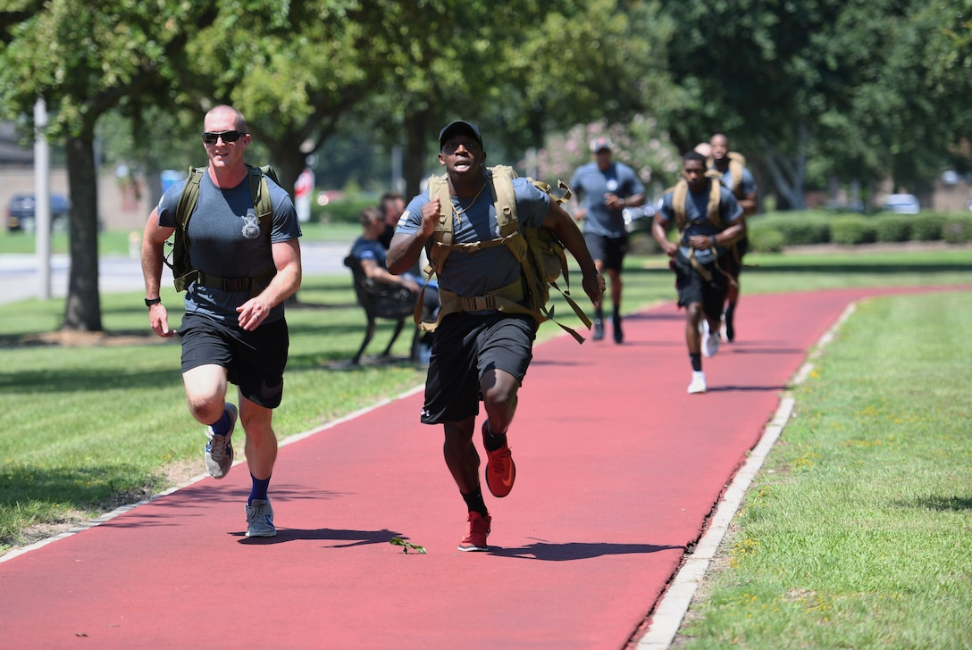 U.S. Air Force Staff Sgt. Jesse Daniel, 81st Security Forces Squadron confinement NCO in charge, and Staff Sgt. Tradarius Christian, 81st SFS police services, lead their team in running a lap while carrying ruck sacks during the 81st SFS Defender's Challenge Ruck on the Crotwell Track on Keesler Air Force Base, Mississippi, Aug. 16, 2019. The competition, consisting of 11 four-person teams, completing seven obstacles, was one of several events in recognition of The Year of the Defender. (U.S. Air Force photo by Kemberly Groue)