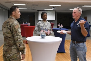 a man talks to two airmen