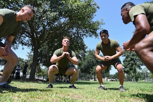 Members of the Keesler Marine Detachment team participate in the air squats portion of the 81st Security Forces Squadron Defender's Challenge Ruck near the Crotwell Track on Keesler Air Force Base, Mississippi, Aug. 16, 2019. The competition, consisting of 11 four-person teams, completing seven obstacles, was one of several events in recognition of The Year of the Defender. (U.S. Air Force photo by Kemberly Groue)