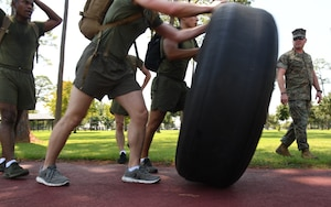 U.S. Marine Staff Sgt. Brandon Mersereau, Keesler Marine Detachment instructor, watches as members of the Keesler MARDET team participate in the tire flipping portion of the 81st Security Forces Squadron Defender's Challenge Ruck on the Crotwell Track on Keesler Air Force Base, Mississippi, Aug. 16, 2019. The competition, consisting of 11 four-person teams, completing seven obstacles, was one of several events in recognition of The Year of the Defender. (U.S. Air Force photo by Kemberly Groue)
