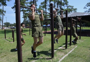 Members of the Keesler Marine Detachment team participate in the pull-up portion of the 81st Security Forces Squadron Defender's Challenge Ruck near the Crotwell Track on Keesler Air Force Base, Mississippi, Aug. 16, 2019. The competition, consisting of 11 four-person teams, completing seven obstacles, was one of several events in recognition of The Year of the Defender. (U.S. Air Force photo by Kemberly Groue)