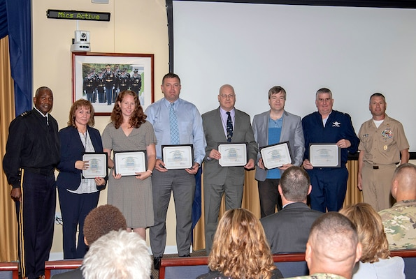 A line of employees holding award certificates