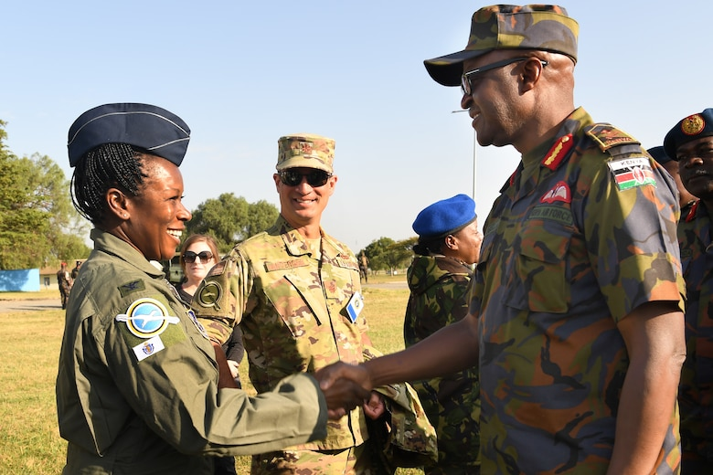 Col. Melinda Swanson, 102nd Medical Group commander, shakes hands with Maj. Gen. Francis C. Ogolla, commander of the Kenya air force, following the opening ceremony for African Partnership Flight Kenya 2019 at Laikipia Air Base, Kenya, August 20, 2019.
