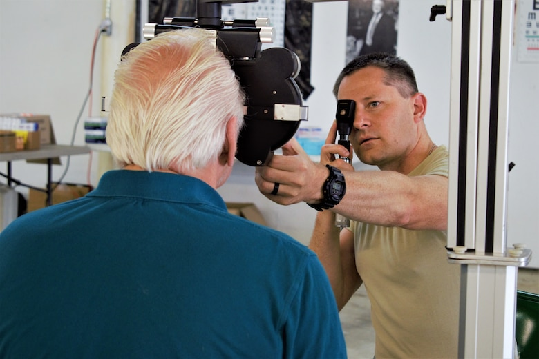 U.S. Air Force Maj. Joshua Metzger, optometrist, 127th Medical Group, Selfridge Air National Guard Base, Michigan, examines a patient during Appalachian Care Innovative Readiness Training 2019 at Wise County Fairgrounds, Wise, Virginia, Aug. 18, 2019. Appalachian Care IRT takes place Aug. 16-29 to provide medical, dental, optometry and veterinary care to assist local health and municipal authorities in addressing underserved and unmet community health and civic needs in Wise, Virginia, while simultaneously conducting deployment and readiness training for military personnel. Innovative Readiness Training is the only hands-on training opportunity authorized to operate within the United States. During Appalachian Care IRT, medical operations are staged at one physical location at Wise County Fairgrounds. Units also conduct critical mission training and logistical movement to simulate hands-on deployment readiness operations and health care delivery in times of crisis, conflict or disaster. (U.S. Air National Guard photo by 1st Lt. Andrew Layton)