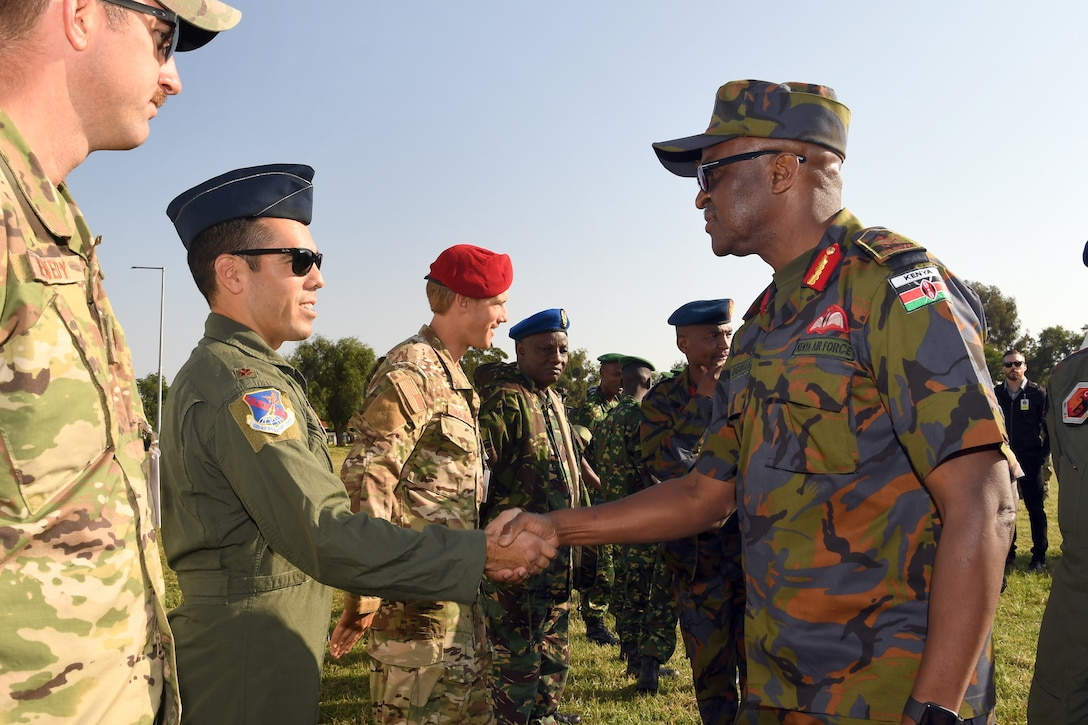 Maj. Anibal Aguirre, U.S. Air Forces in Europe and Air Forces Africa personnel recovery coordination cell director, shakes hands with Maj. Gen. Francis C. Ogolla, commander of the Kenya air force, following the opening ceremony for African Partnership Flight Kenya 2019 at Laikipia Air Base, Kenya, August 20, 2019.
